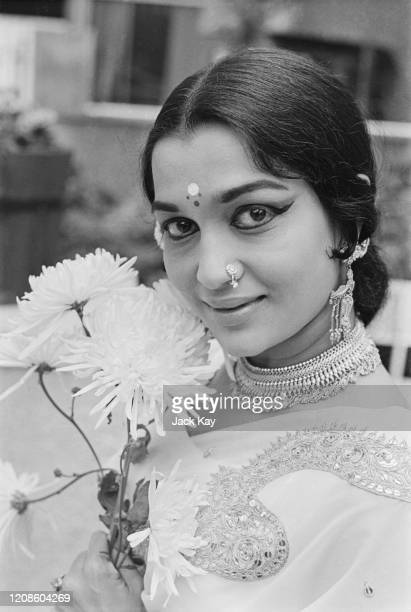 Indian actress Asha Parekh wearing a nose piercing, earrings and a necklace as she poses beside a flower, United Kingdom, 16th June 1972.