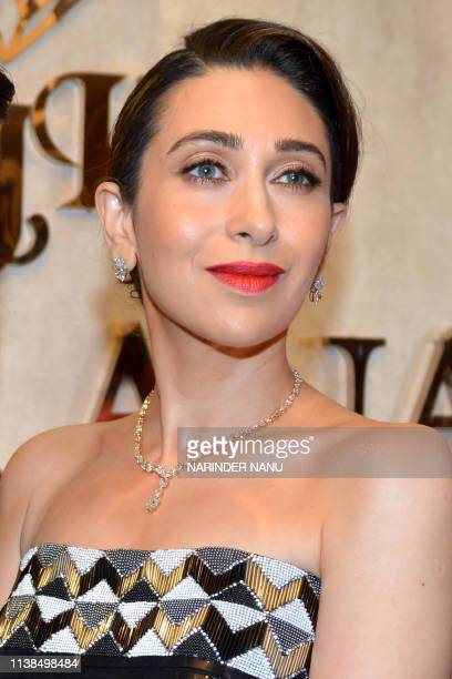 Indian actress Karisma Kapoor looks on as she poses for photographs during a promotional event for the jewellery brand 'Forevermark' launch at...