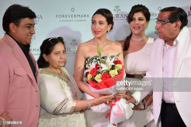 Indian actress Karisma Kapoor receives flowers during a promotional event for the jewellery brand 'Forevermark' launch at Khurana Jewellery House, in...