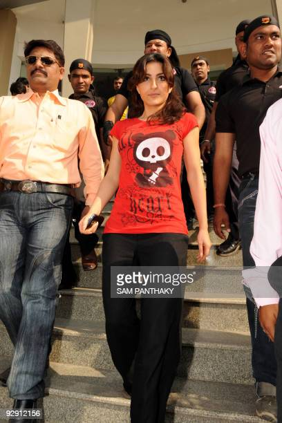 Indian actress Soha Ali Khan is escorted by private security as she exits the Grand Bhagwati's Cafe Piano, in Ahmedabad on November 9, 2009....