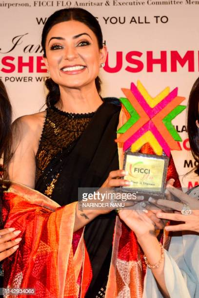 Indian actress Sushmita Sen holds a trophy as she attends an event on the eve of Mother's Day celebrations organised by the Federation of Indian...