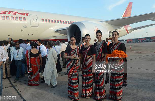 Indian Air air hostesses hold marigold flowers to welcome Air India's first Boeing 787 Dreamliner from Charleston USA after it landed at Indira...