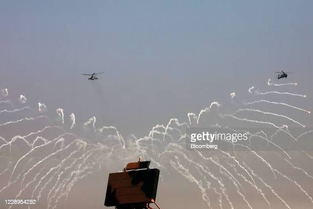 Indian Air Force Apache helicopters drop flares in a flying display during Air Force Day Parade at Hindon Air Force Station in Ghaziabad, Uttar...