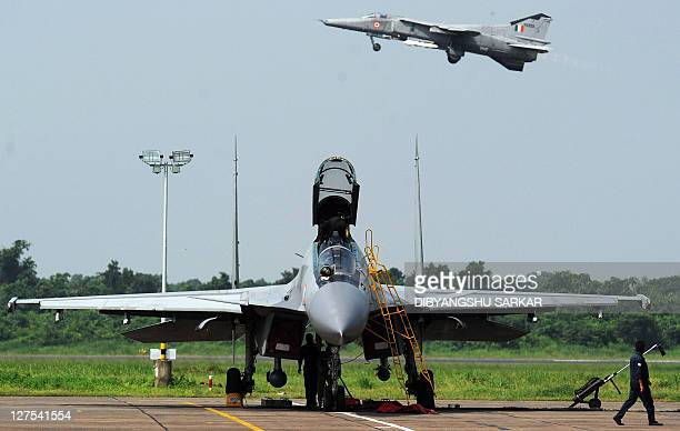 Indian Air Force engineers prepare a Sukhoi30 fighter jet ahead of a drill as a MIG27 flies overhead during a drill for Air Force Day celebrations in...