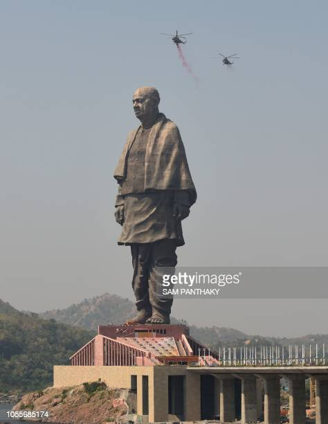 TOPSHOT Indian Air Force helicopters shower rose petals on the Statue Of Unity the world's tallest statue dedicated to Indian independence leader...