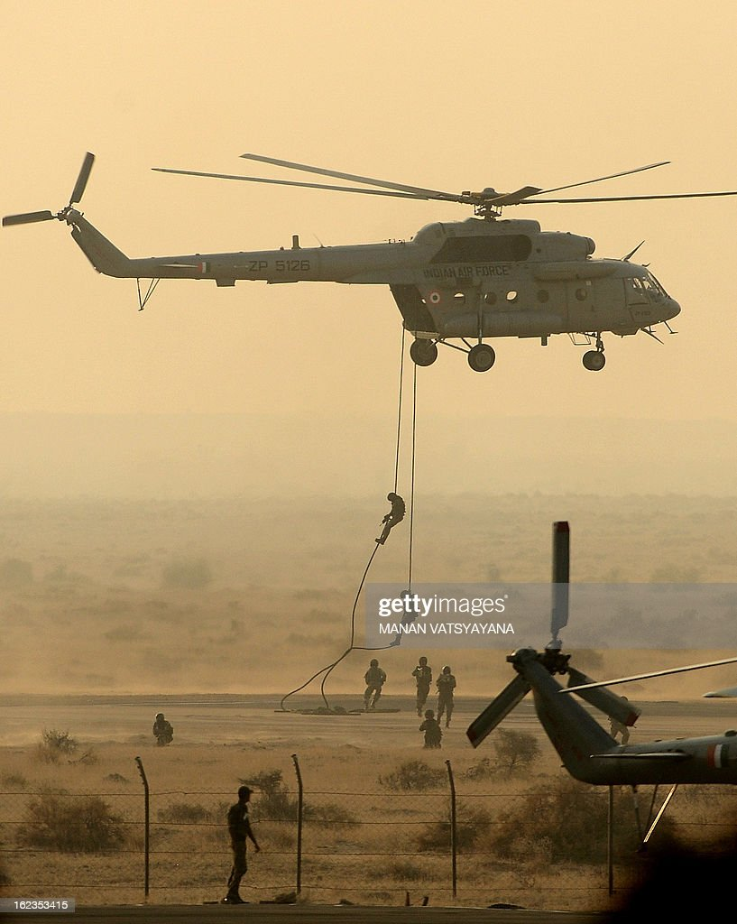 Indian Air Force (IAF) paratroopers drop from a Mi-17 helicopter during the Iron Fist 2013 exercise in Pokhran on February 22, 2013. IAF held the Iron Fist 2013 exrecise to showcase its operational capabilities during day,dusk and night taking out simulated targets with precison laser-guided weaponry.