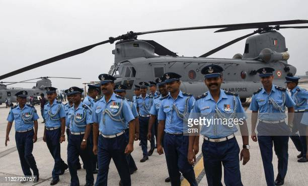 Indian Air Force personnel walk next to a CH47F Chinook helicopter at an induction ceremony at the Air Force Station Chandigarh in Chandigarh on...