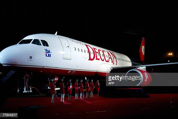 Indian air hostesses pose alongside a Deccan aircraft during an event to announce the merger of Air Deccan and Kingfisher Airlines in Mumbai late 28...