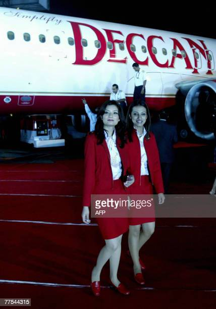 Indian air hostesses walk alongside a Deccan aircraft during an event to announce the merger of Air Deccan and Kingfisher Airlines in Mumbai late 28...