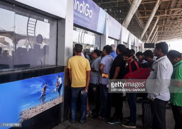 Indian air passengers stand in a queue to buy or reschedule air tickets at Biju Patnaik International Airport in Bhubaneswar in India's eastern...