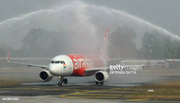 Indian airport fire trucks make a water spray archway to welcome an AirAsia airplane after it land on its inaugural flight from New Delhi to Bagdogra...