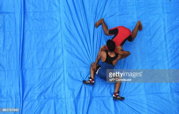 Indian amateur wrestlers participate in a friendly wrestling competition on a makeshift ring at the junction of a busy road organised as part of...