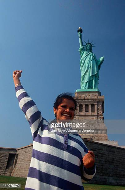 Indian American woman raising arm Statue of Liberty New York