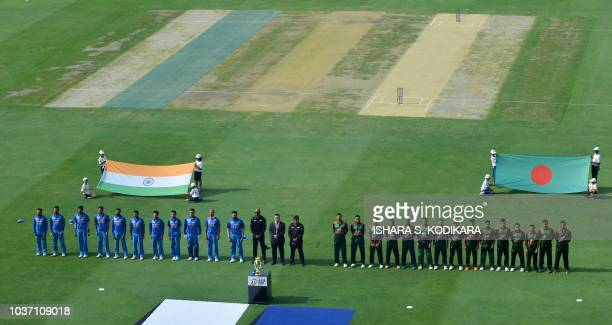 Indian and Bangladesh players line up for the national anthems prior to the start of the one day international Asia Cup cricket match between...