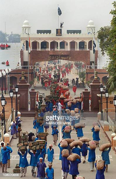Indian and Pakistan porters exchange goods at the international India Wagah Border 27 November 2006 as trucks are not permitted to cross the border...