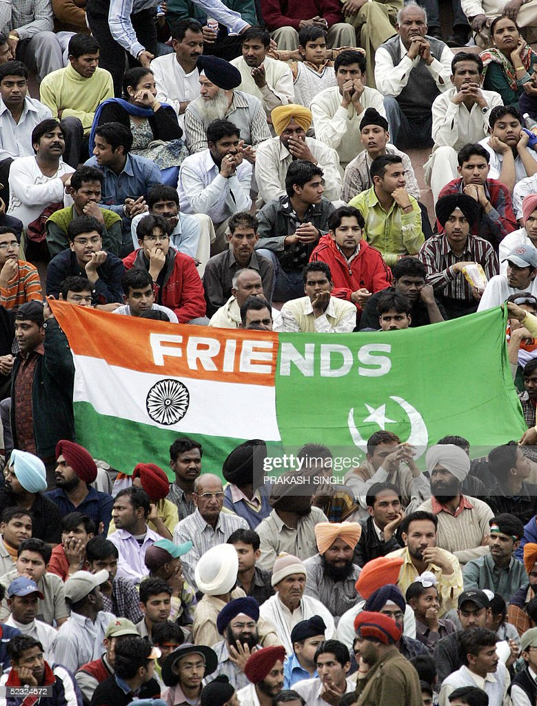 Indian and Pakistani cricket fans sit next to a flag calling for friendship between their two countries during the second day of the first Test match.