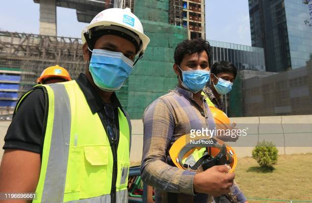 Indian and Sri Lankan construction workers walk out of a megaconstruction site wearing face masks following the Corona virus outbreak in China at...
