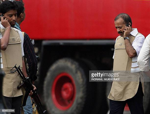 Indian Anti Terror Squad officials speak on their mobile telephones after a successful mission at The Taj Mahal hotel in Mumbai on November 29 2008...