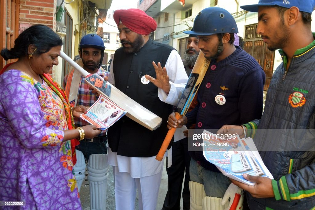 Indian Apna Punjab Party candidate for the Punjab Legislative Assembly Narinder Singh and supporters carry a bat Singh`s election symbol during a...