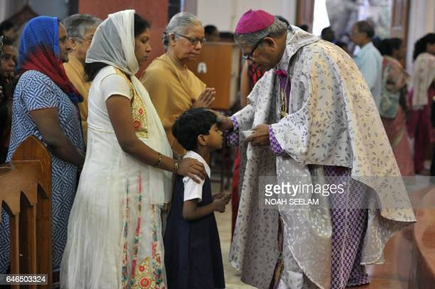 Indian Archbishop of Hyderabad Thumma Bala marks the symbol of the cross with ash on the forehead of a young Christian devotee during an Ash...