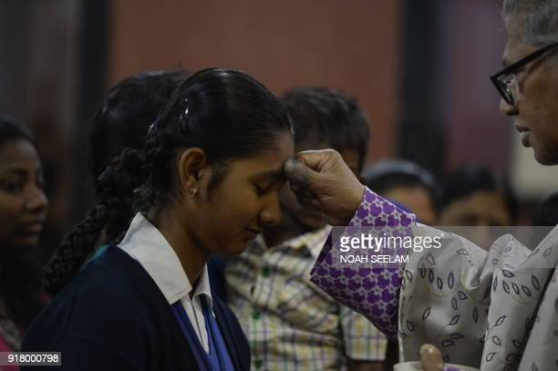 Indian Archbishop of Hyderabad Thumma Bala marks the symbol of the cross with ash on the forehead of a student during an Ash Wednesday service at...