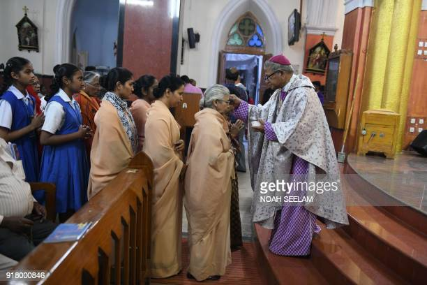 Indian Archbishop of Hyderabad Thumma Bala marks the symbol of the cross with ash on the forehead of a nun during an Ash Wednesday service at Saint...
