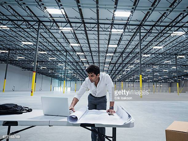 Indian architect using laptop in empty warehouse