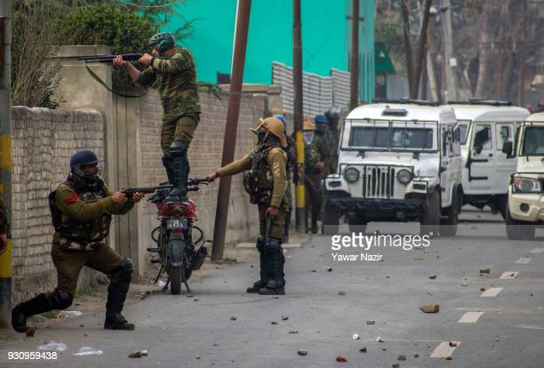 Indian armed forces fire rubber bullets and metal pellets with their shotguns at Kashmiri Muslim mourners carrying the body of Eesa Fazili a Kashmiri...