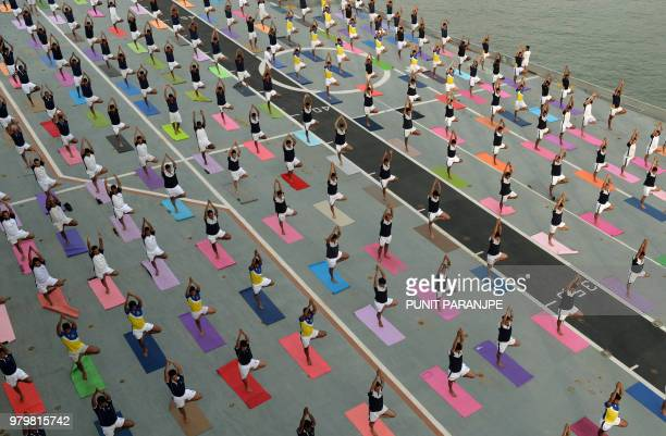 TOPSHOT Indian Armed Forces personnel take part in a yoga sesssion to mark International Yoga Day on the Indian Navy aircraft carrier INS Viraat...