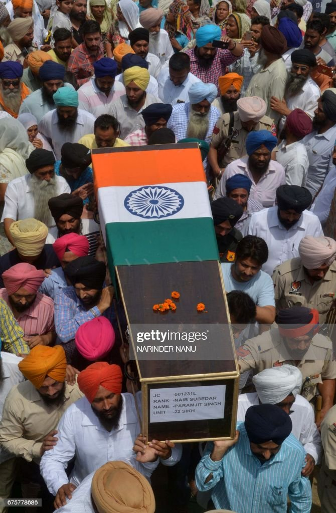 Indian Army and Punjab Police personnel and relatives carry the coffin of Indian Army soldier Paramjeet Singh ahead of his funeral at Vein Pein...