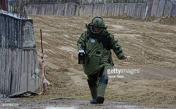 Indian Army Bomb disposal squad in a protective bomb suit try to defuse an Improvised Explosive Device before it is neutralised on March 11 2016 in...