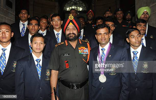 Indian Army Chief General Bikram Singh poses with Olympic silver medal winner Vijay Kumar and other athletes during an award function for Indian Army...