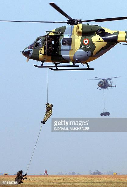 Indian Army commandos slither down a rope from an overhead helicopter at the Yehlanka airforce base on the outskirts of Bangalore 06 February 2005...