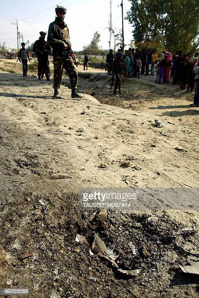 Indian army look at the crater in the road after a car bomb explosion in the Nowgam area on the outskirts of Srinagar 02 November 2005 A suicide...