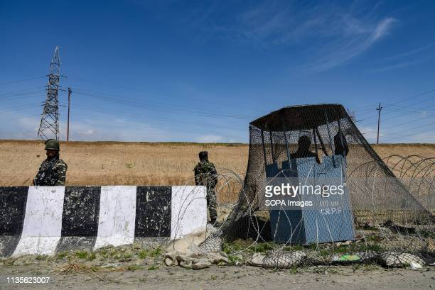 Indian army men are seen standing alert to safeguard the movement of Indian convoys at the National Highway on the outskirts of Srinagar The Indian...