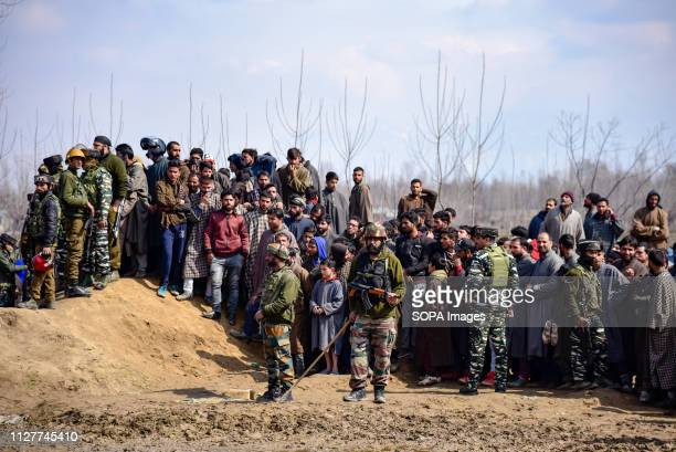 Indian army men are seen standing on guard as the kashmiri villagers gathered near the wreckage of an aircraft that crashed in Budgam area. A...