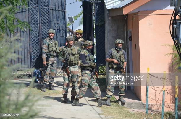 Indian army men take cover near the building where last suspected militant was believed to be holed up in Humhama on the outskirts of Srinagar the...