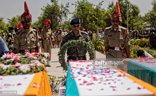 Indian Army officer lays wreath on the coffins containing the bodies of the killed Border Security Force soldiers during their wreathlaying ceremony...