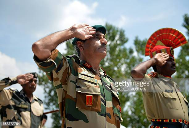 Indian Army officer Satish Dua salutes the coffins of three colleagues during a wreathlaying ceremony at BSF headquarters in Srinagar on August 9...