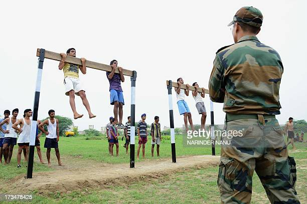 Indian army officer watches candidates perform pullups during a physical fitness test at an Indian Army recruitment rally at Khasa some 15 Kms from...