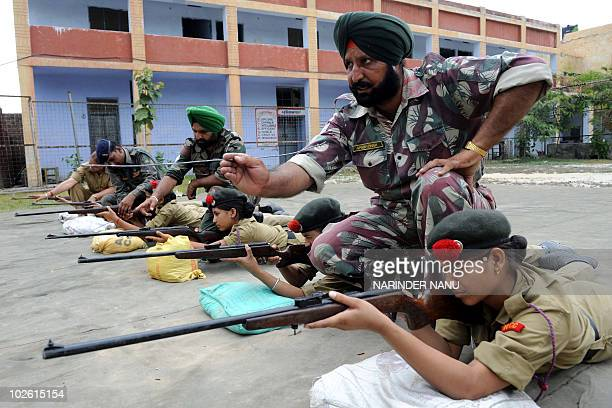 Indian Army officers Amrik Singh and Swinder Singh advise National Cadet Corps students during rifle training at a weapons training camp held at...