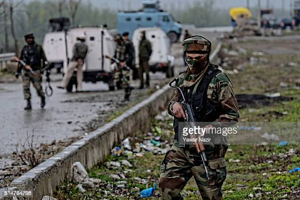 Indian Army officers soldiers stand guard near the site of an Improvised Explosive Device before it is neutralised on March 11 2016 in Srinagar the...