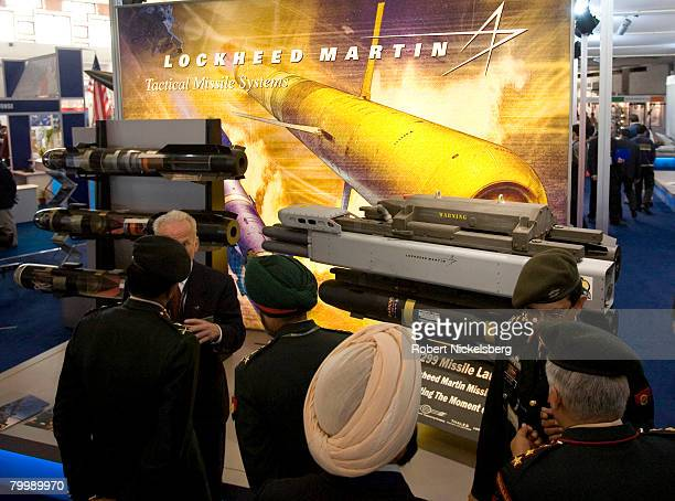 Indian Army officers with the Ministry of Defense listen to a Lockheed Martin weapons salesman left partially hidden explain the Hellfire missile...