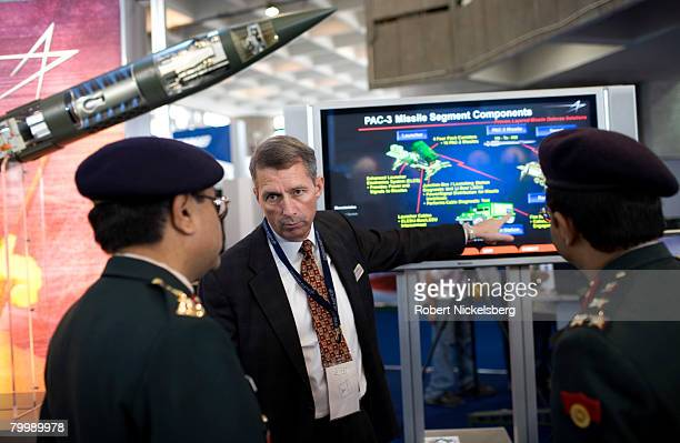 Indian Army officers with the Ministry of Defense listen to a Lockheed Martin weapons salesman center explain a mobile missile system February 18...