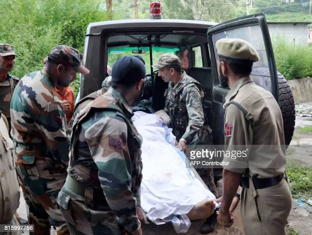 Indian army personnel and policemen move the body of a soldier reportedly killed along the line of control between India and Pakistan to a morgue in...