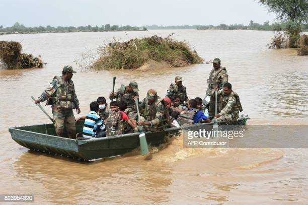 Indian Army personnel bring to safety stranded flood victims at Khariya village of Banas Kantha district some 230 km from Ahmedabad on July 28 2017...