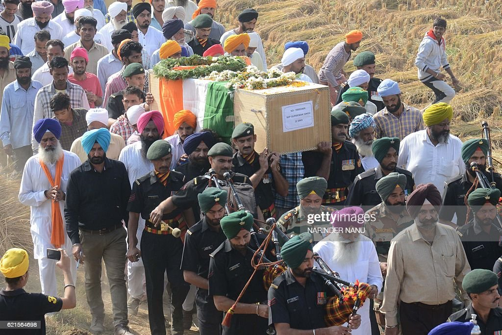 Indian army personnel carry a coffin with the body of Indian soldier Gursewak Singh for his funeral at Warana village about 35km from Amritsar on...