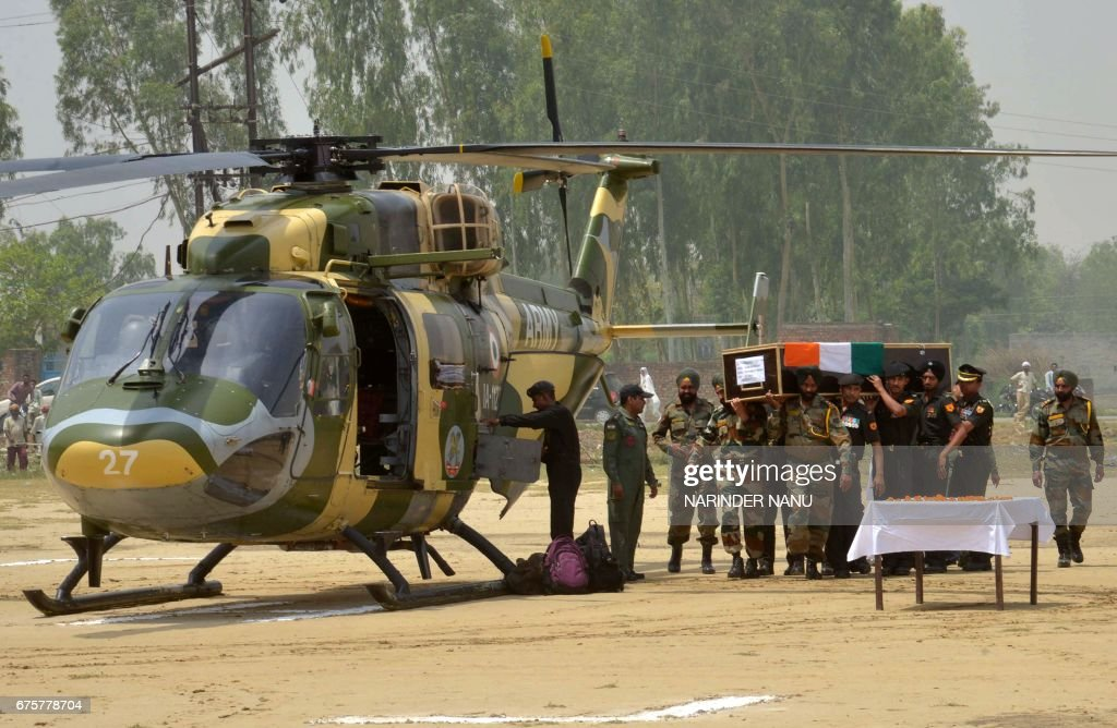 Indian Army personnel carry the coffin of Indian Army soldier Paramjeet Singh ahead of his funeral at Vein Pein village some 45kms from Amritsar on...