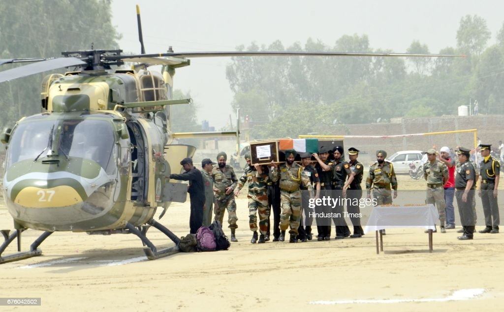 Indian Army personnel carry the coffin of Indian Army soldier Paramjit Singh ahead of his funeral at Vein Pein village some 45 km from Amritsar on...