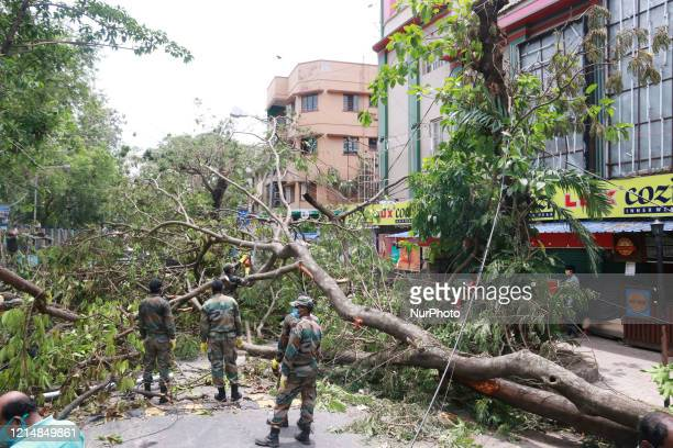 Indian Army personnel deploy to clean roads from fallen tree electric lines and others following the landfall of cyclone Amphan in Eastern India city...
